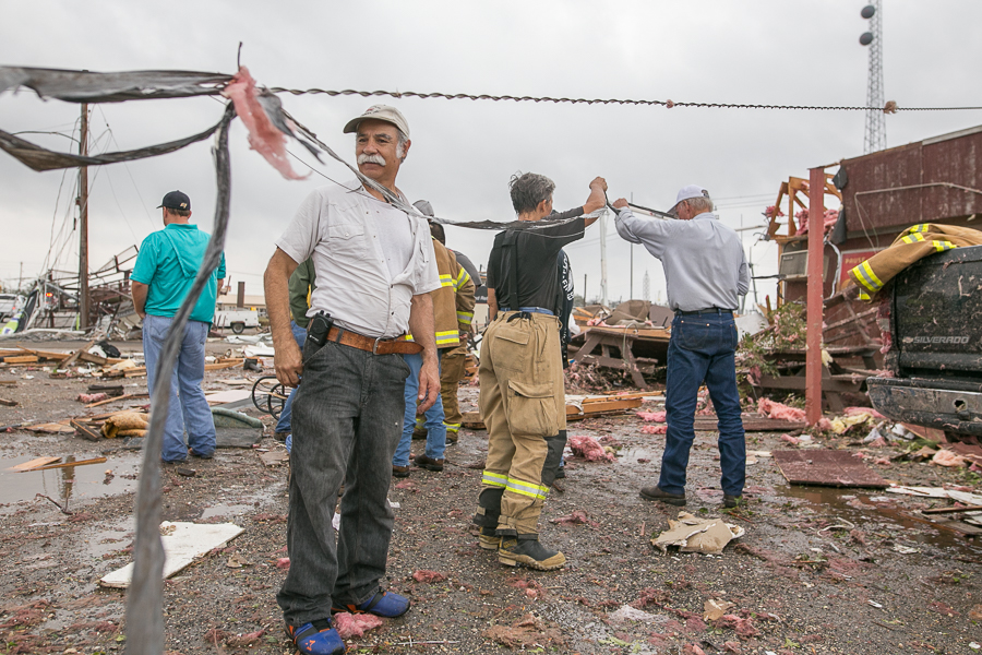 Floresville Volunteer Firefighter Arturo Quintana overlooks the damage caused by the tornado. Photo by Scott Ball.