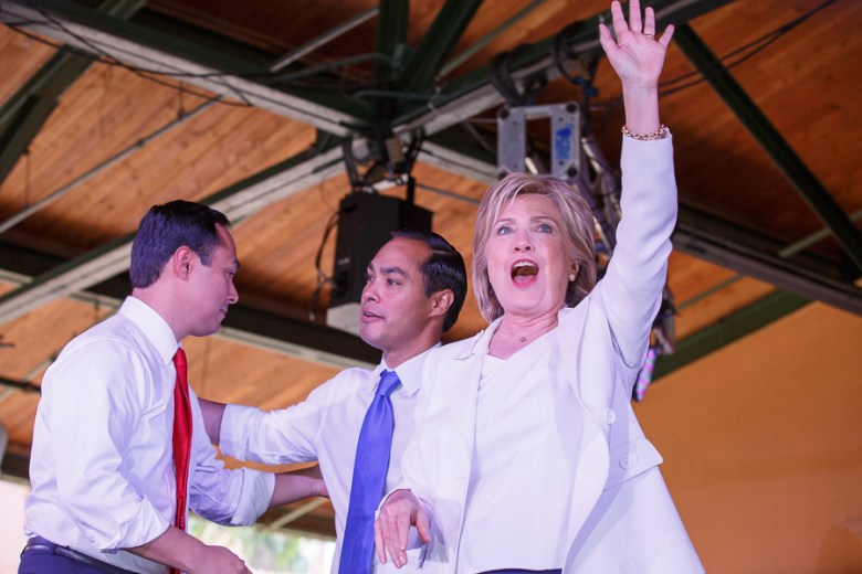 Hillary Clinton (right) waves as brothers Julián and Joaquín Castro meet on stage. Photo by Scott Ball.