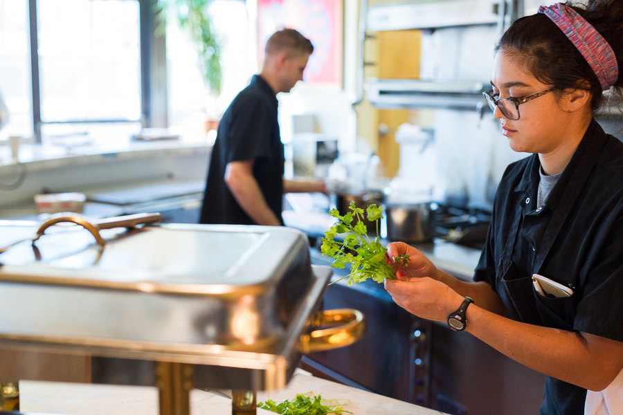 Alex Zrinski (right) picks cilantro in preparation of dinner service as John Carpenter prepares a dish in the background. Photo by Scott Ball.