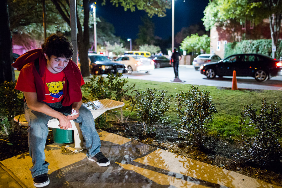 Student Leo Gonzalez, 18, waits for a ride at the bus stop near police activity at the University of Incarnate Word. Photo by Scott Ball.