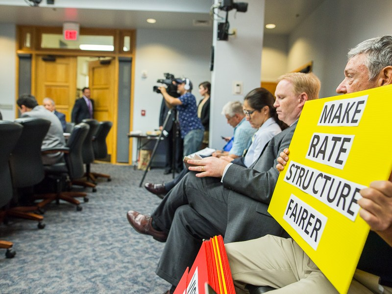 Alan Montemoyar holds up a sign in opposition to the rate structure of the Vista Ridge pipeline. Photo by Scott Ball.