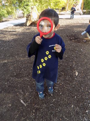 A child plays with a magnifying glass. Photo courtesy of Pre-K for SA.