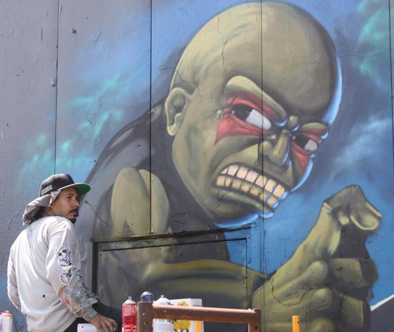 The artist known as 'Real Tres' will travel from his home base of Monterrey, Mexico to participate in the urban paint festival. He is pictured here while painting a mural in Houston at an event called the Meeting of Styles. Photo by Kay Richter.