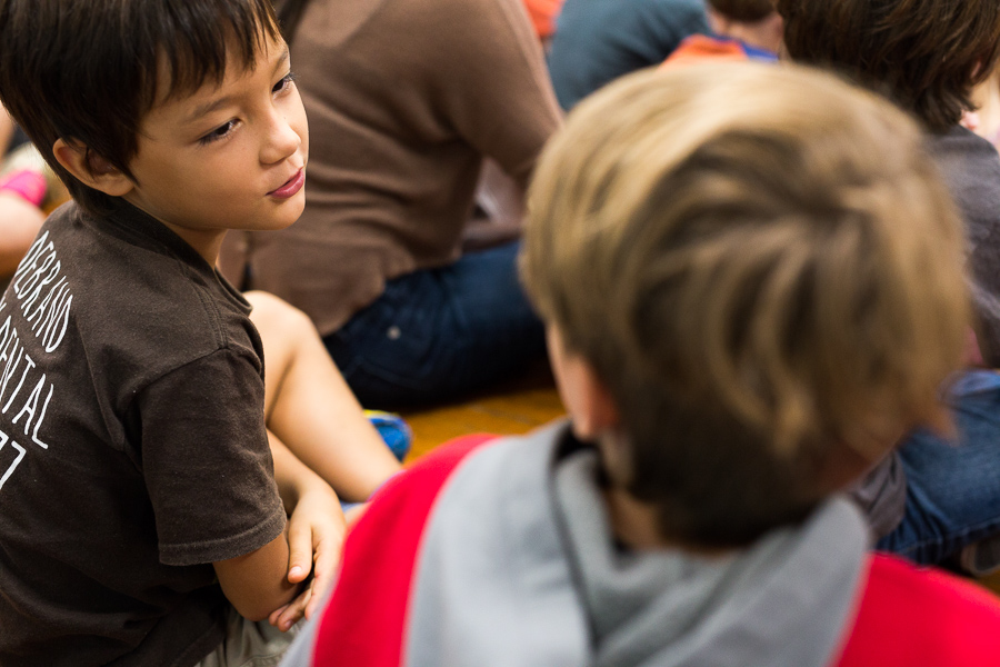 Students look at each other while singing during circle time. Photo by Scott Ball.