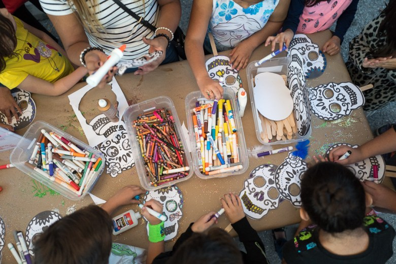 Children circle around a table while crafting sugar skulls. Photo by Scott Ball.