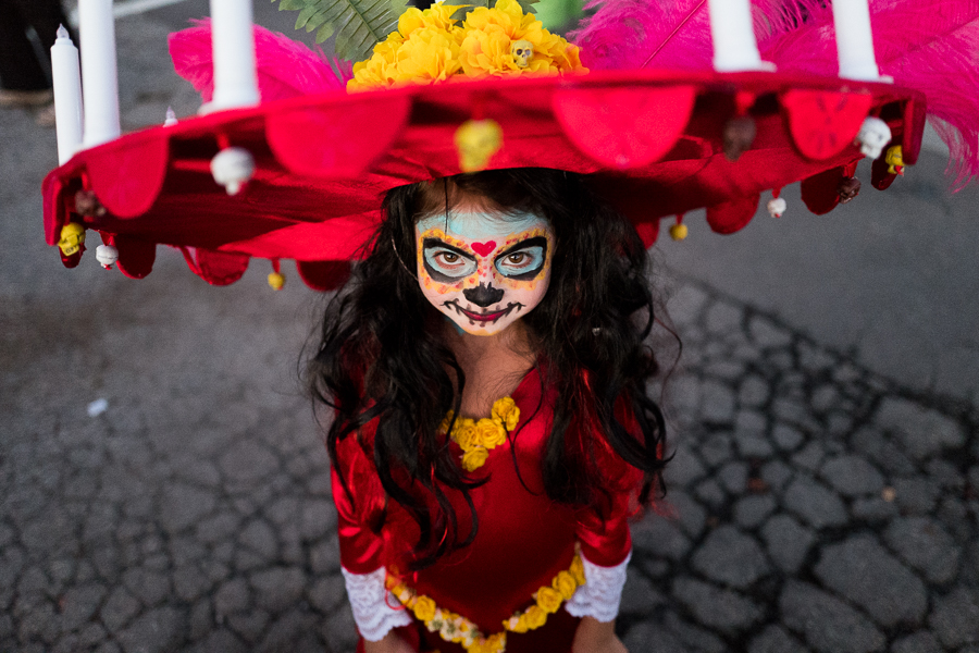 Madelyn, 5, wears a decorative costume for Day of the Dead complete with candles on her ultra wide brimmed hat. Photo by Scott Ball.