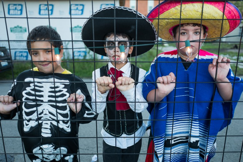 Nicolas, 10 (left), Hunter, 9 (middle), Charles, 11 pose for a photo behind the Guadalupe Cultural Arts Center. Photo by Scott Ball.
