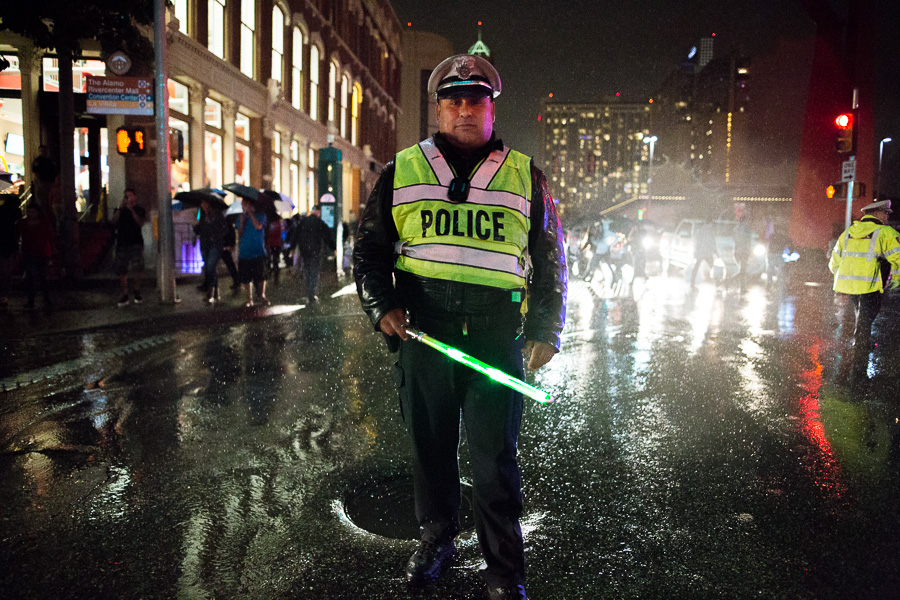 San Antonio Police Officer Rendon stands in the street after being handed a novelty light saber to direct traffic. Photo by Scott Ball.