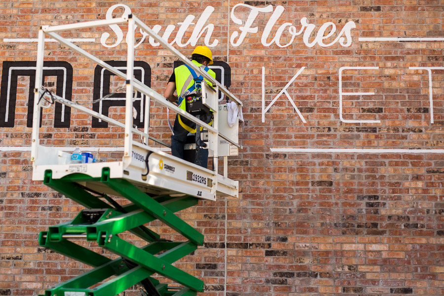 A painter draws black outline around the white letters of a hand painted sign facing South Flores Street. Photo by Scott Ball.