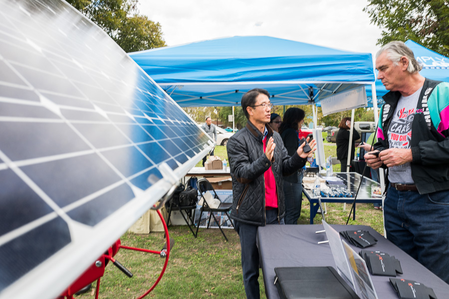 Thomas Kim of Mission Solar Energy explains the benefit of solar power to San Antonio resident Mike Bursheim. Photo by Scott Ball.