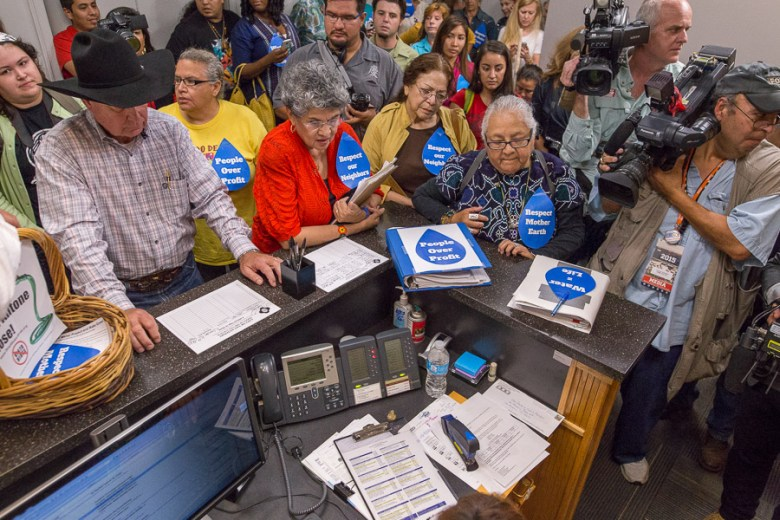 Protestors surround the reception desk at City Hall. Photo by Scott Ball.