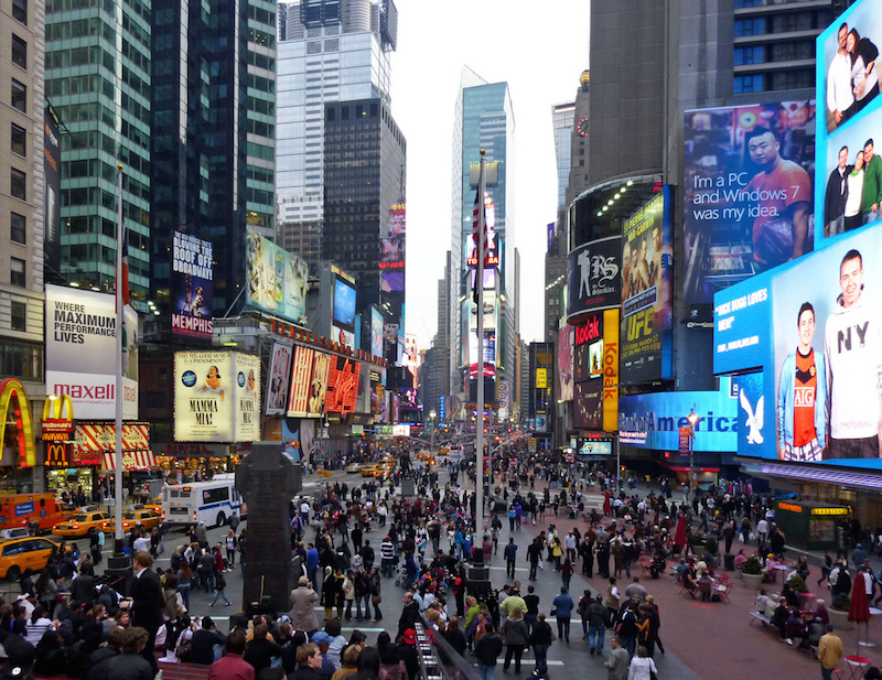 A crowded Times Square plaza. Photo by Flickr user Payton Chung.
