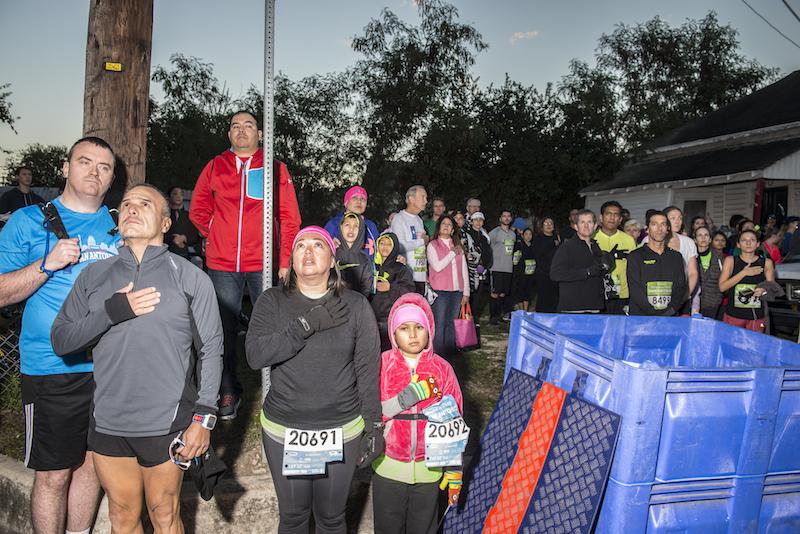 Runners listen to the national anthem before the start of the San Antonio Rock 'N' Roll Marathon. Photo by Matthew Busch.