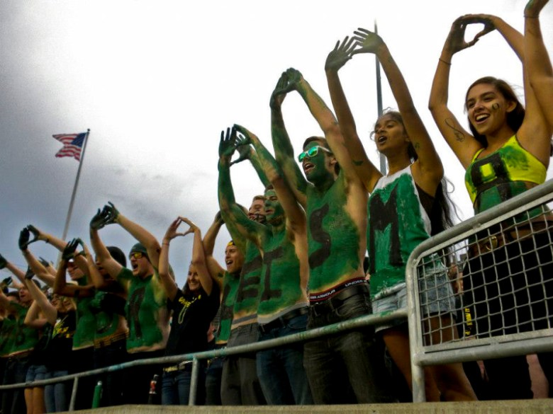 "University of Oregon fans hold up ""O"" signals at a game in Eugene. Photo by Kathryn Boyd-Batstone."