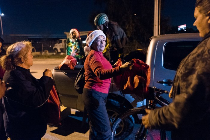 Norma Banda (center) hands out backpacks full of goods to those in need. Photo by Scott Ball.