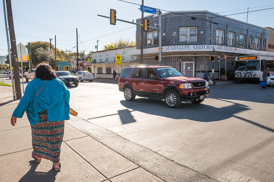 A pedestrian takes the cross walk at the corner of Brazos Street and Guadalupe Street in front of the Progreso Building.