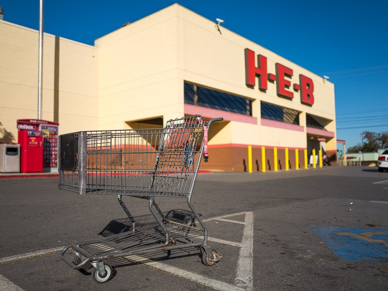 An empty grocery cart sits in the parking lot in front of H-E-B in the near east side. Photo by Scott Ball.