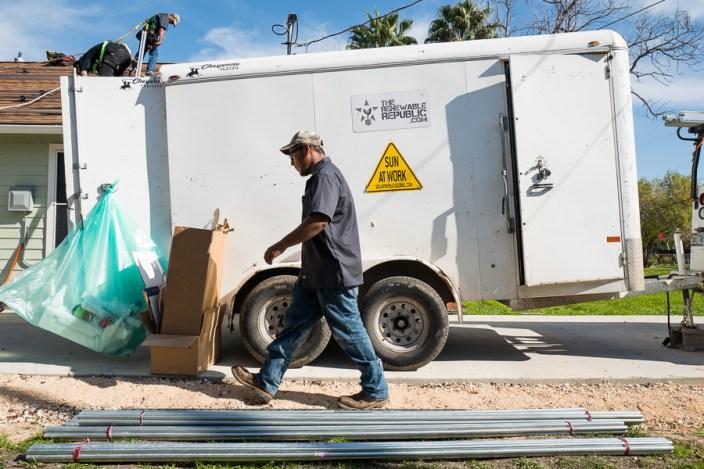 Mark Estrada of The Renewable Republic walks across the job site as Luis Medellin works above. Photo by Scott Ball.