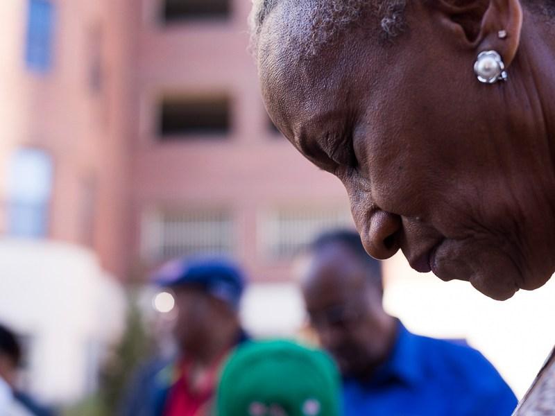Minnie Hill bows her head as a prayer is said. Photo by Scott Ball.