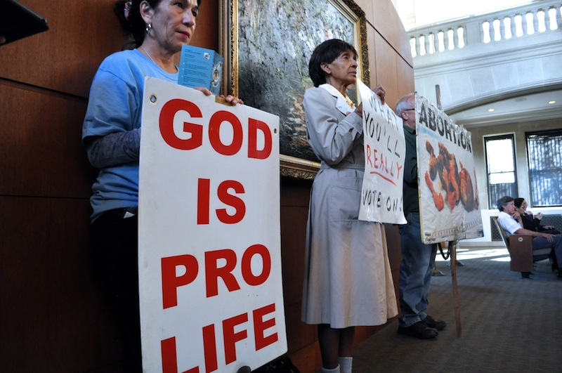 (From left) San Antonio Family Association member Norma Reyes, Dolores Ferrell of the Pro-life Association of St. Paul's Church, and Robert Cornwell hold signs in protest of abortion and of the proposed zoning change. Photo by Iris Dimmick.