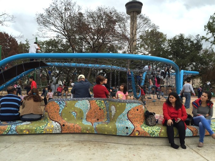 "Friends and family sit on mosaic seating while kids of all ages play on the blue ""Boomerang"" climbing and slide feature in Yanaguana Garden. Photo by Robert Rivard."