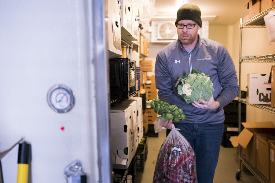 Shaun Lee, founder of Truckin' Tomato, prepares a box of produce for delivery. Photo by Kathryn Boyd-Batstone