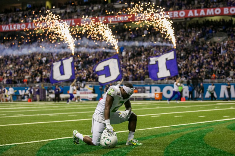 Oregon quarterback Vernon Adams kneels down at the start of the Valero Alamo Bowl. He left the game injured after a helmet-to-helmet collision.