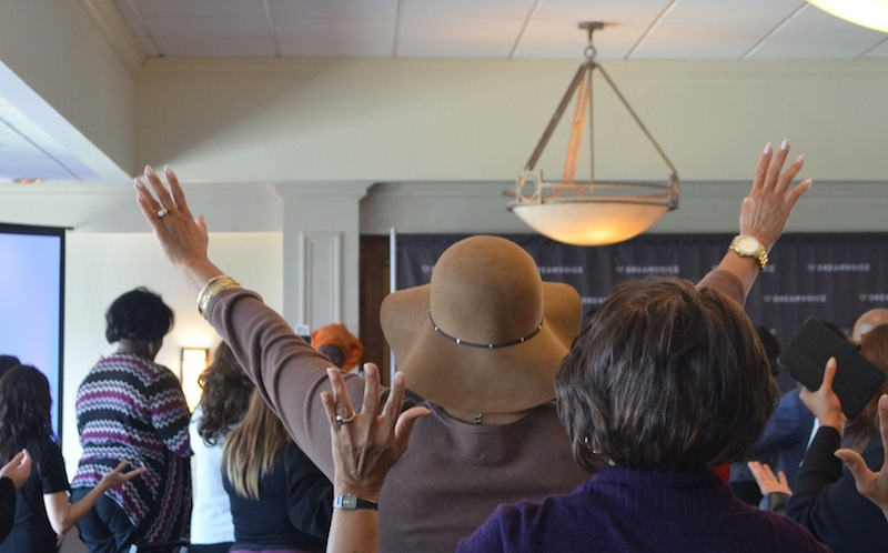 Men and women lift their arms in prayer during the DreamVoice awards luncheon. Photo by Camille Garcia.