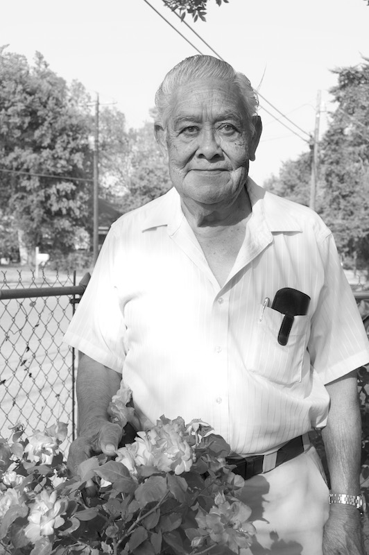 Eddy Rangel, owner of Eddy's Convenience Store in Lockhart, Texas stands in his rose garden. Photo by Lea Thompson.