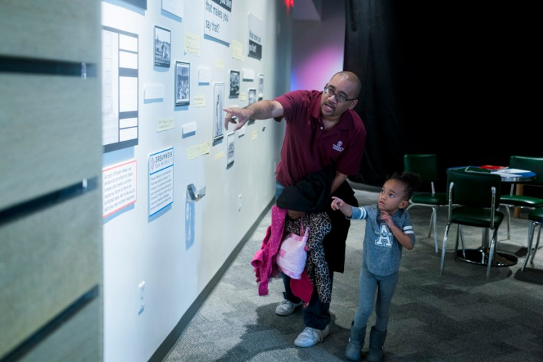 Wilson Terrell Jr. explains the iconic photo of Ruby Bridges, the first black child to attend an all-white elementary school, to his daughter Nia Ray Terrell. These photos are part of a DreamWeek Exhibit at the DoMeum. Photo by Kathryn Boyd-Batstone