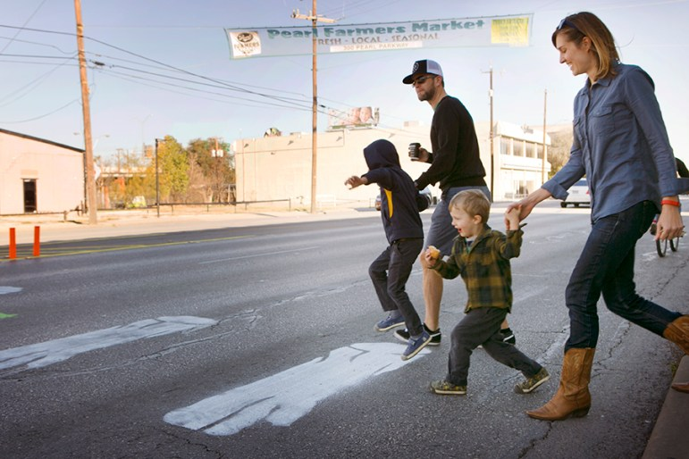 The Yaden family uses the chalk created crosswalk at the intersection of Pearl Parkway and Broadway Street. Photo by Kathryn Boyd-Batstone