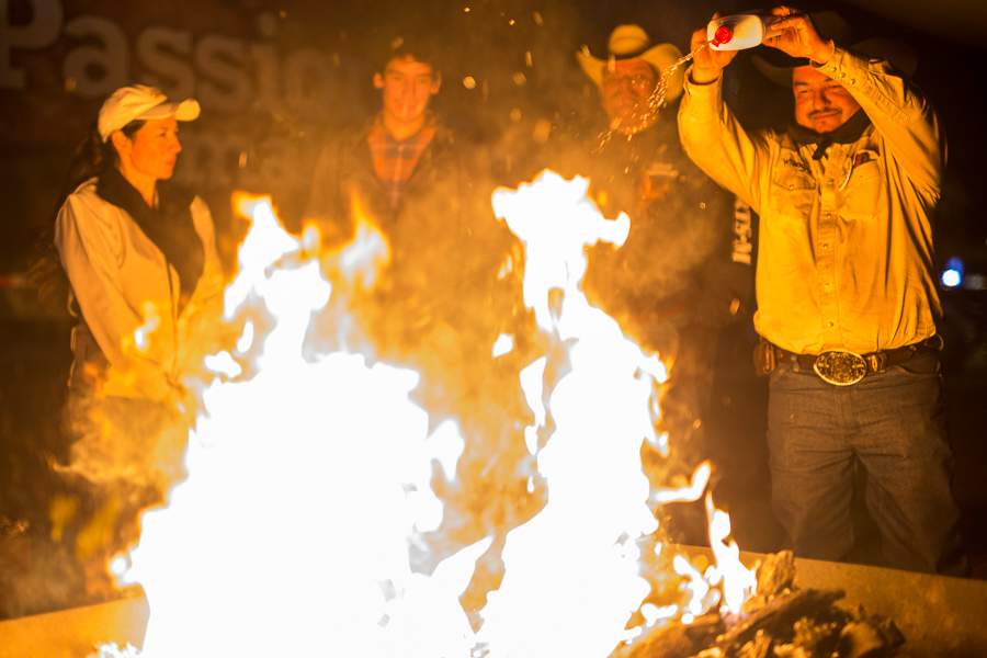 Pasqual Valadez Junior squirts lighter fluid on open flames used to keep grills hot. Photo by Scott Ball.