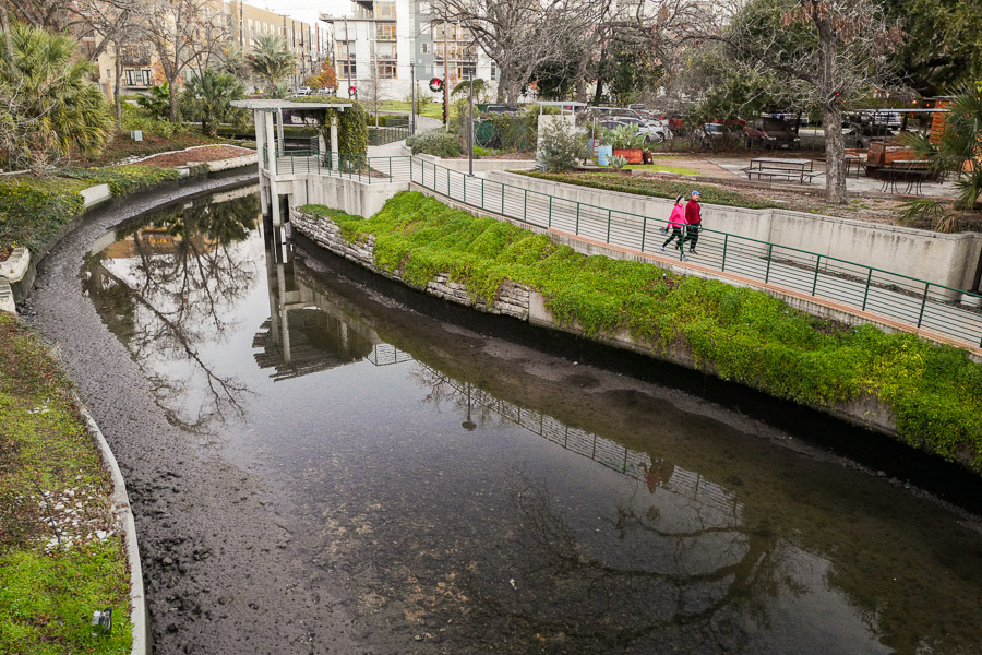 Pedestrians walk along the museum reach portion of the San Antonio River. Photo by Scott Ball.