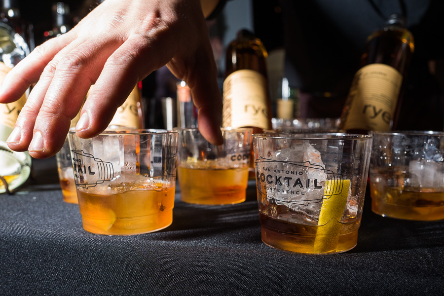 A bartender arranges a plethora of rye based cocktails at his booth. Photo by Scott Ball.