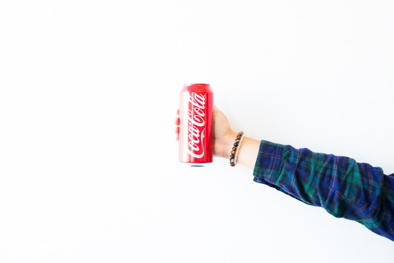 A 16 ounce can of Coca-Cola is held in the hand. The drink includes 52 grams of sugar. Photo by Scott Ball.