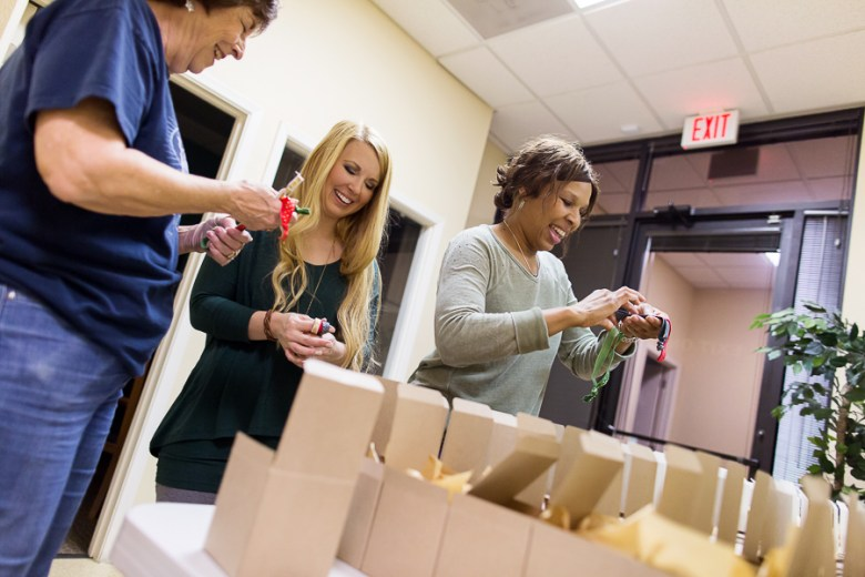 Donna Davis, Kayla Moilanen, and Lucy Williams add hair bands to each gift box. Photo by Rachel Chaney.