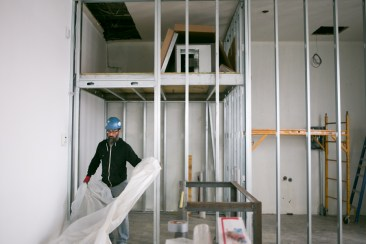 Carlos Sanchez works on preparing the space for a wrap around L-shaped coffee bar. Photo by Kathryn Boyd-Batstone