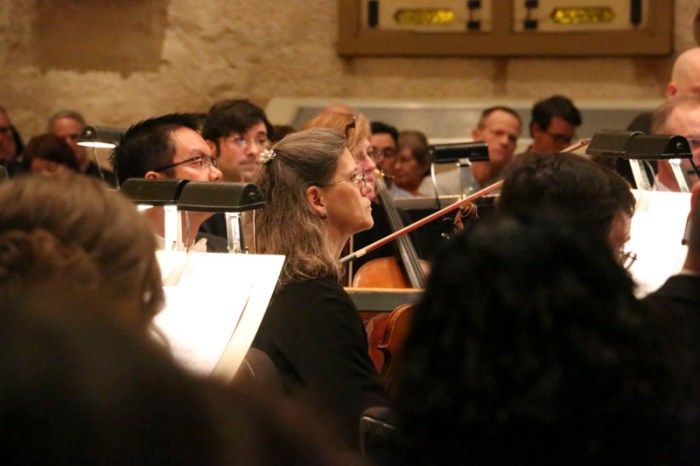 A member of the San Antonio Symphony listens intently as violinist and conertmaster, Eric Gratz, introduces the second half of the Baroque series. Photo by Bria Woods.