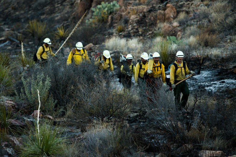 Members of Los Diablos emerge from the basin, tools in hand and tired from the day of fighting wildland fires. Photo by Scott Ball.