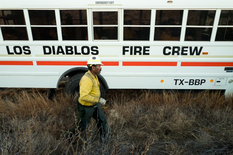 A member of Los Diablos walks to the entrance of the transportation bus after unloading his gear. Photo by Scott Ball.