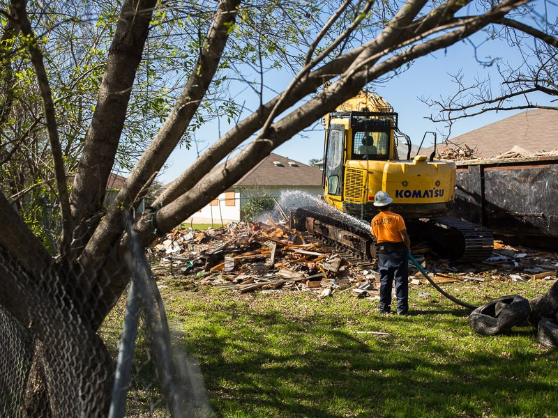 A demolition worker sprays a recently destroyed house with water. Photo by Scott Ball.