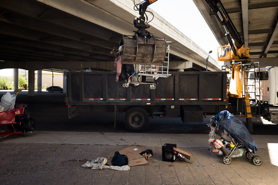 A crane operated by the City of San Antonio's Transportation and Capital Improvements Department hoists a grocery cart filled with the belongings to be disposed of. Photo by Scott Ball.