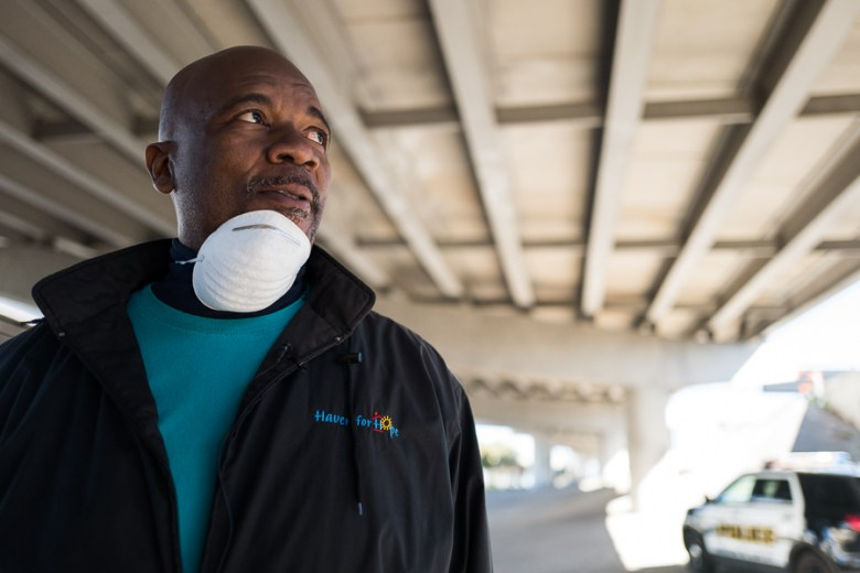 """Haven for Hope Outreach Coordinator Ron Brown watches as city workers dispose of homeless possessions. """"Whey they're there, the look on their face is unbelievable."""" Photo by Scott Ball."""