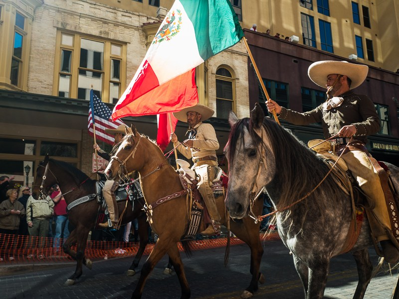 Charro's hold American, Texas, and Mexican flags during the Western Heritage Parade. Photo by Scott Ball.