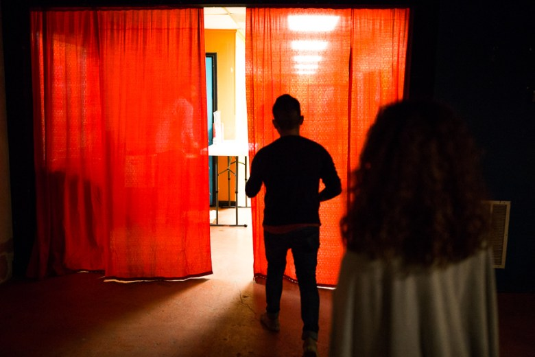 Guests walk through a red curtain at Freight Gallery. Photo by Scott Ball.