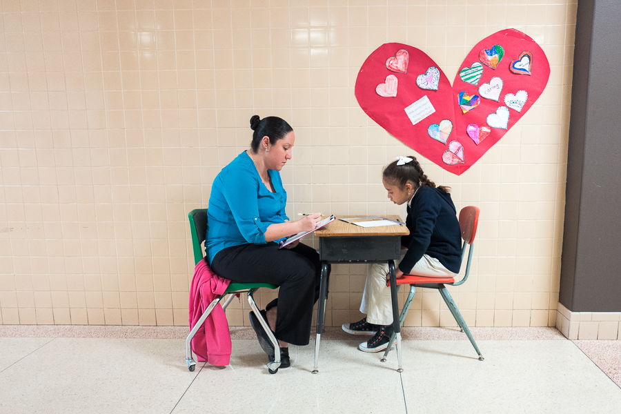 Stewart Elementary Teacher Mrs. Montez gives a reading lesson to student Jeimy Rojas in the schools hallway. Photo by Scott Ball.
