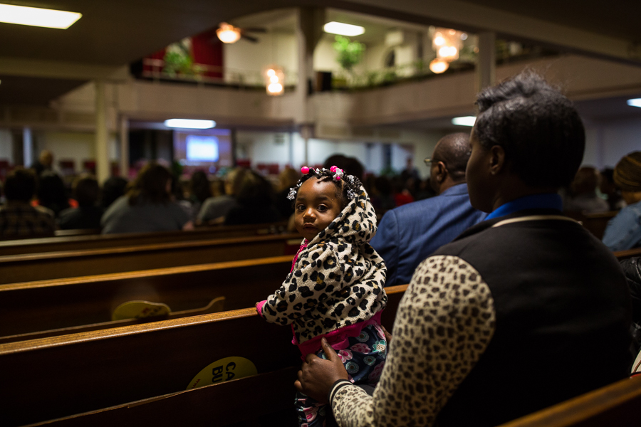 Community members take their seats in church pews as the meeting begins. Photo by Scott Ball.