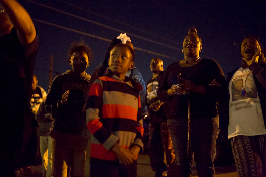 The Marquise Jones family yells as they congregate on the street outside the New Light Baptist Church. Photo by Scott Ball.