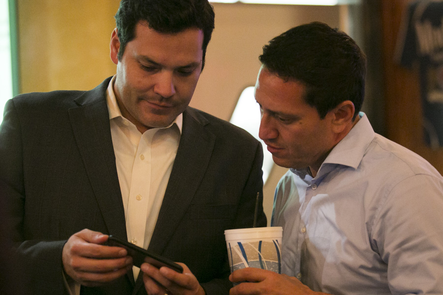 State Rep. Justin Rodriguez (left) looks over early election results with Trey Martinez Fischer. Photo by Kathryn Boyd-Batstone.