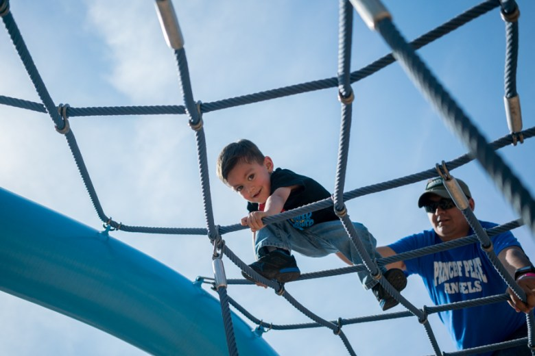 Xavier plays on a jungle gym with his dad at the Mokingbird Fest. Photo by Kathryn Boyd-Batstone